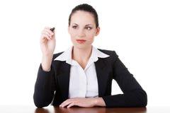 Mujer de negocios que intenta escribir en el espacio de la copia, sentándose por la tabla. Imagenes de archivo
