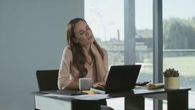 Mujer de negocios que intenta relajarse en lugar de trabajo Mujer cansada que trabaja en el ordenador metrajes