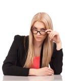 Mujer de negocios que le mira sobre los vidrios Imagenes de archivo