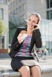 Mujer de negocios que llama el teléfono y la consumición Imagen de archivo libre de regalías