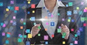 Mujer de negocios que lleva a cabo el dispositivo futurista rodeado por los iconos coloridos Imagen de archivo libre de regalías