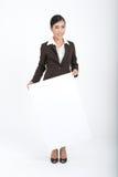 Mujer de negocios que lleva a cabo la muestra en blanco Imagen de archivo libre de regalías