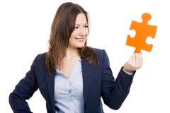 Mujer de negocios que lleva a cabo un pedazo del rompecabezas imagen de archivo libre de regalías