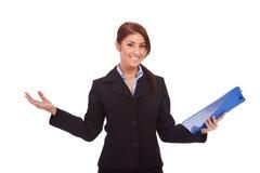 Mujer de negocios que lleva a cabo un sujetapapeles y dar la bienvenida Foto de archivo libre de regalías