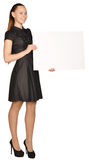 Mujer de negocios que lleva a cabo a una tarjeta blanca en blanco Foto de archivo