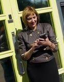 Mujer de negocios que manda un SMS en el teléfono móvil Imagen de archivo libre de regalías