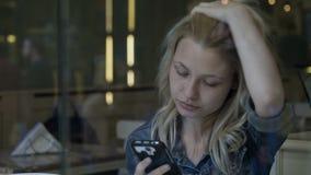 Mujer de negocios que manda un SMS en medios sociales en smartphone mientras que come el helado en esperar del pub metrajes