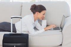Mujer de negocios que miente en el sofá con el ordenador portátil y la maleta Fotografía de archivo libre de regalías