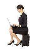 Mujer de negocios que mira el cuaderno que se sienta en la maleta, aislada imagenes de archivo