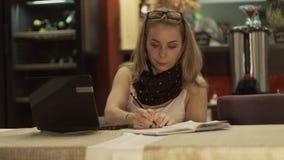 Mujer de negocios que mira en el cuaderno de la pantalla y que escribe en el diario de moda en café almacen de metraje de vídeo