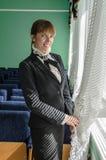 Mujer de negocios que mira hacia fuera la ventana y la sonrisa Imágenes de archivo libres de regalías