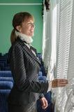 Mujer de negocios que mira hacia fuera la ventana y la sonrisa Imagen de archivo