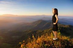 Mujer de negocios que mira la montaña y la puesta del sol cuando éxito Foto de archivo