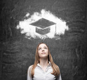Mujer de negocios que mira la nube con el sombrero de la graduación sobre la cabeza Imagen de archivo libre de regalías
