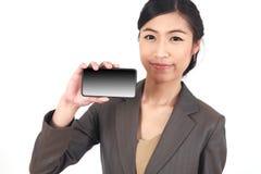Mujer de negocios que muestra la exhibición en blanco del teléfono celular móvil del tacto Foto de archivo libre de regalías