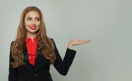 Mujer de negocios que muestra la mano abierta vac?a en el fondo blanco Concepto de la sonrisa, del negocio y de la educación de l imagenes de archivo