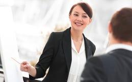 Mujer de negocios que muestra una información del equipo del negocio sobre el flipchart Imagenes de archivo