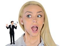 Mujer de negocios que parece sorprendida en pequeño hombre Imagen de archivo