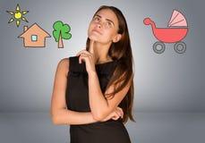 Mujer de negocios que piensa sobre el cochecillo y la casa con Foto de archivo libre de regalías