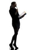 Mujer de negocios que piensa sosteniendo la silueta de los ficheros de las carpetas Imagen de archivo
