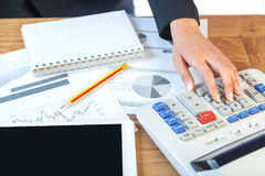 Mujer de negocios que pone su mano en la calculadora, el negocio y el inve Imagen de archivo libre de regalías