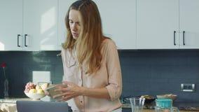 Mujer de negocios que prepara a la persona femenina relajada del desayuno que comprueba el teléfono móvil