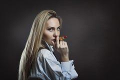Mujer de negocios que presenta con el lápiz labial como cigarro Imagen de archivo