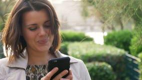 Mujer de negocios que ríe en la sonrisa que habla del teléfono almacen de video