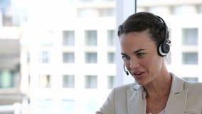 Mujer de negocios que ríe mientras que habla en auriculares