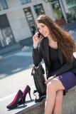 Mujer de negocios que recorre en las escaleras que llaman el teléfono Fotografía de archivo libre de regalías