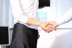 Mujer de negocios que sacude las manos con un hombre en apagado Imágenes de archivo libres de regalías
