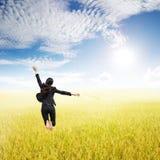 Mujer de negocios que salta en campos del arroz y cielo amarillos del sol Imagen de archivo libre de regalías