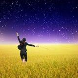 Mujer de negocios que salta en campos y estrella amarillos del arroz Imagenes de archivo