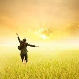 Mujer de negocios que salta en campos y puesta del sol amarillos del arroz el día del éxito Foto de archivo