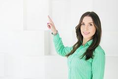 Mujer de negocios que señala en el espacio de la copia en el fondo blanco Foto de archivo