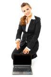 Mujer de negocios que señala en la pantalla en blanco de las computadoras portátiles Imagen de archivo libre de regalías