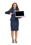 Mujer de negocios que señala en la pantalla en blanco del ordenador portátil Imágenes de archivo libres de regalías