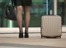Mujer de negocios que se coloca con el bolso y la maleta Imagenes de archivo