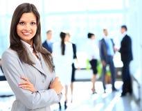 Mujer de negocios que se coloca con su personal en fondo en la oficina