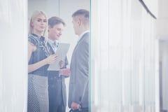 Mujer de negocios que se coloca con su personal en fondo en la oficina moderna imagen de archivo