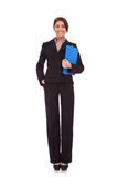 Mujer de negocios que se coloca con su sujetapapeles Foto de archivo libre de regalías
