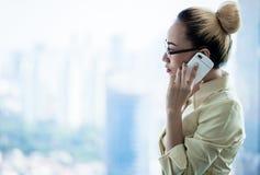Mujer de negocios que se coloca en la ventana del rascacielos que hace llamada Fotografía de archivo libre de regalías