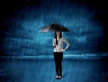 Mujer de negocios que se coloca en lluvia con un paraguas Imagenes de archivo
