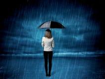 Mujer de negocios que se coloca en lluvia con un paraguas Imágenes de archivo libres de regalías