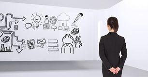 Mujer de negocios que se coloca en un cuarto 3D con un gráfico conceptual en la pared Imagen de archivo libre de regalías