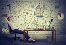 Mujer de negocios que se relaja en su escritorio en su oficina Imagen de archivo libre de regalías