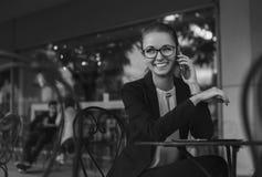Mujer de negocios que se sienta en café y que habla en el teléfono y el smil Imagen de archivo