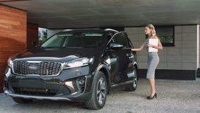 Mujer de negocios que se sienta en coche rico Mujer hermosa que camina para ennegrecer el auto almacen de video