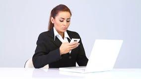 Mujer de negocios que se sienta en el escritorio y el teléfono que habla almacen de metraje de vídeo