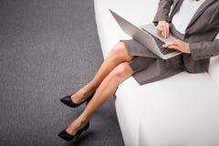 Mujer de negocios que se sienta en el sofá con el ordenador en su revestimiento imagen de archivo